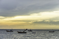 Fishing boat floating on sea with sunset sky Stock Photography