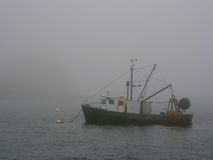 Fishing boat in fog Stock Photo