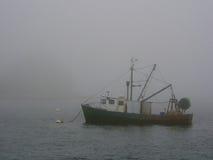Fishing boat in fog stock photo