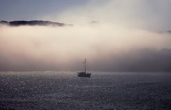 Fishing Boat In the Fog. Isolated royalty free stock photography
