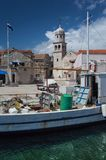 Fishing boat in front of Åepurine village. Old, messy fishing boat in front of idyllic mediterranean village with beautiful stonework on houses and church royalty free stock photography