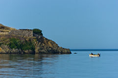 Fishing boat in front of an old roman fotress at morning, Sithonia Royalty Free Stock Images