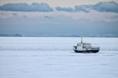 Fishing boat frozen in the ice Royalty Free Stock Photos