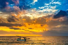 Sunset on the Lombok Indonesia. A fishing boat goes to the ocean in the evening. Bright colorful orange sun hidden in dense blue clouds over the Bali Sea. A Royalty Free Stock Images