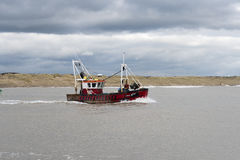 Fishing boat going out from Rye harbour Sussex UK Royalty Free Stock Image