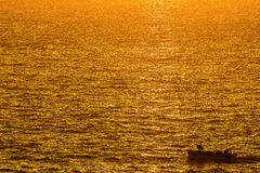 Fishing boat on a golden ocean. The sun rises and the ocean glows with golden color Royalty Free Stock Photos