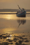 Fishing Boat grounded at low tide in Poole Harbour Stock Image