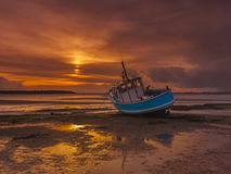 Fishing Boat grounded at low tide in Poole Harbour Stock Photography