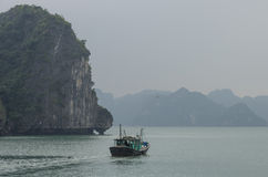 Fishing boat in Ha Long bay, Vietnam. Cloudy winter weather Stock Photos