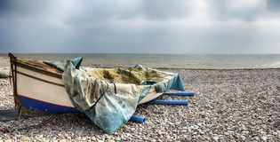 Fishing Boat on Beach at Budleigh Salterton. Fishing boat half draped with tarpaulin on the beach at Budleigh Salterton in Devon Stock Photography