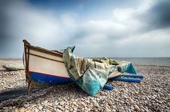 Fishing Boat on Beach at Budleigh Salterton. Fishing boat half draped with tarpaulin on the beach at Budleigh Salterton in Devon Stock Photo