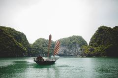 Fishing boat in Halong Bay. Among limestone islands topped by rainforests in emerald water. World heritage seascape Stock Photo