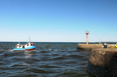 Fishing boat at harbor mouth Stock Images