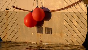 Fishing boat in harbor with red buoys hanging from the back with depth level. Marking and calm waves motion with warming sunshine stock video footage