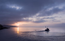 Fishing boat heading out to sea Royalty Free Stock Photo