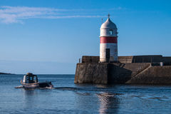 Fishing boat heading out to sea past harbor and lighthouse Royalty Free Stock Photos
