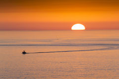Fishing Boat Heads Home At End Of Day in Florida. This fishing boat heads home from fishing in front of a beautiful sunset at Clearwater Beach, Florida in the Stock Image