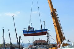Fishing boat hoisted by a crane Royalty Free Stock Photos