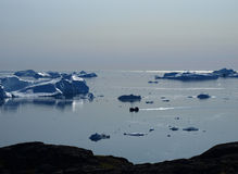 Fishing boat in Ilulissat Icefjord, Greenland. Fishing boat at dusk in front of the icebergs at the mouth of Ilulissat Icefjord Royalty Free Stock Image