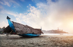 Fishing boat in India. Fishing boat with palm tree leaves on the beach in the morning at lighthouse background in Kovalam, Kerala, India royalty free stock photo