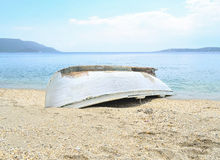 White fishing boat. Inverted fishing boat on the Mediterranean beach Royalty Free Stock Photos