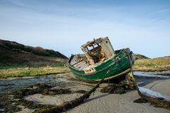 Back of abandoned Fishing Boat. Fishing boat on its side on the beach tide up at low tide Royalty Free Stock Photography