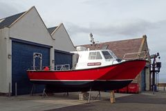 View on a sunny day of a fishing boat outside marine sheds, Lossiemouth, Moray, Scotland, UK. stock photography