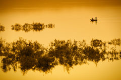 Fishing boat on lake with orange light. A fishing boat with two men on a lake in orange light.  With copy space Stock Photos