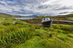 Fishing boat on land in a picturesque environment in front of an inlet at low tide in the landscape of the `Isle of Harris and Lew. Is` island, Scotland, United Royalty Free Stock Photos