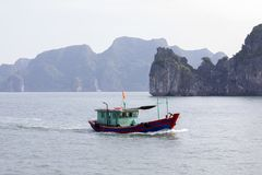 Fishing boat in Lanh Ha Bay. Fishermen live on the waters of Lanh Ha bay with its limestone karsts often covered with lush green vegetation royalty free stock images