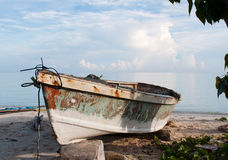 Fishing boat laying on the beach. Sunlit boat on the beach of Jamaica Royalty Free Stock Image