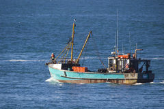 Fishing Boat Leaving the Harbor Stock Photography