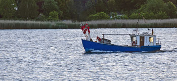 Fishing boat leaving the port Royalty Free Stock Images