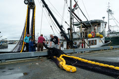 Fishing boat loading nets. Seattle, WA, USA, Oct. 17, 2016: Four men loading a black and yellow fishing net onto commercial fishing boat at Fishermens Terminal Stock Images