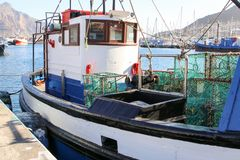 Fishing boat with lobster traps moored in the port in Hout Bay harbor, Cape Town Stock Image