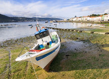 Fishing boat at low tide in Galicia Stock Photos