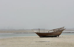A fishing boat in low tide water Stock Image