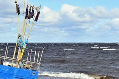 Fishing boat moored on the beach in a stormy weather royalty free stock photography