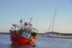 Red fishing boat moored at low water. stock images