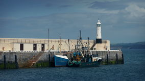 Fishing Boat Moored By Pier And Small Lighthouse. Fishing boat moored a pier with small lighthouse at the end stock video