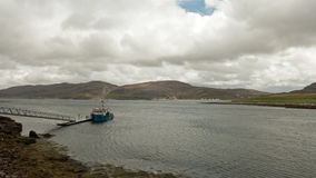 Fishing boat moored on remote Scottish Island. A blue fishing boat moored on a remote Scottish island near Ullapool Stock Images