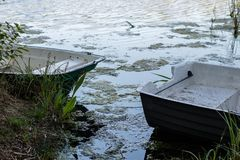 A fishing boat moored to the shore of the lake. Old fishermen& x27;s. Boat prepared for fishing on lakes. Season of the spring Royalty Free Stock Image
