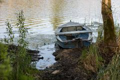 A fishing boat moored to the shore of the lake. Old fishermen& x27;s. Boat prepared for fishing on lakes. Season of the spring Stock Photography