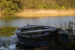 A fishing boat moored to the shore of the lake. Old fishermen& x27;s. Boat prepared for fishing on lakes. Season of the spring Royalty Free Stock Photo