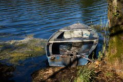 A fishing boat moored to the shore of the lake. Old fishermen& x27;s. Boat prepared for fishing on lakes. Season of the spring Stock Photo