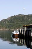 Fishing boat moored by wharf. Or quay with forested mountainside in background, Eide, Norway royalty free stock photography
