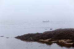 Fishing boat in the morning mist Royalty Free Stock Photos