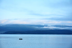 Fishing Boat with Mountains and Low Clouds Stock Image