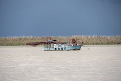 Fishing boat moving through the river on cloudy day Royalty Free Stock Photo