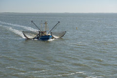 Fishing boat near the beach on the Dutch Wadden Sea Stock Photography